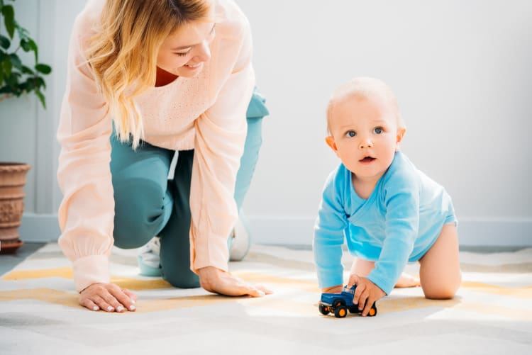 a mother encouraging baby to crawl